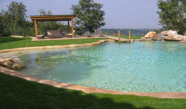 Immagini piscina effetto spiaggia naturale e in roccia for Costruire laghetto in cemento